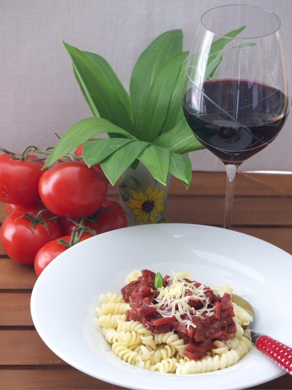 Gemüsebolognese mit Nudeln und einem Glas Rotwein