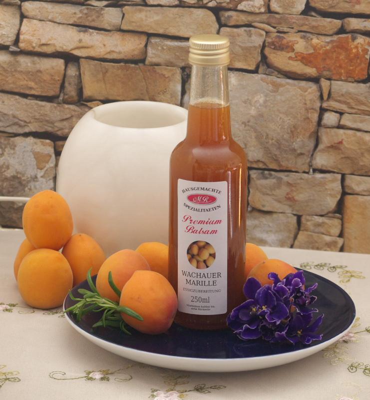 Flasche Wachauer Marillen Balsam Essig auf Teller mit frischen Marillen